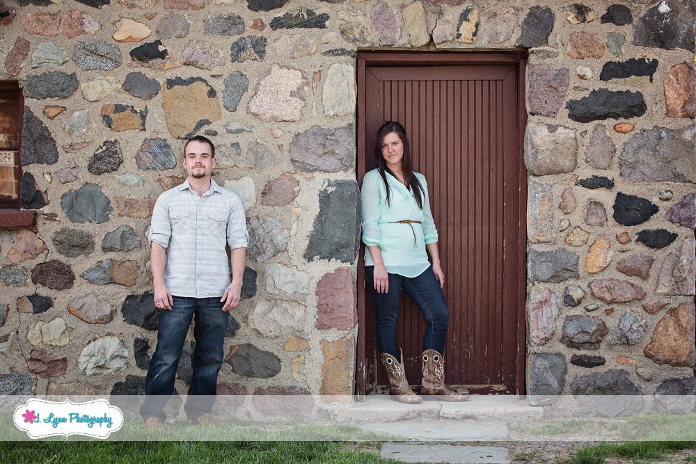 couple standing in front of old farm building