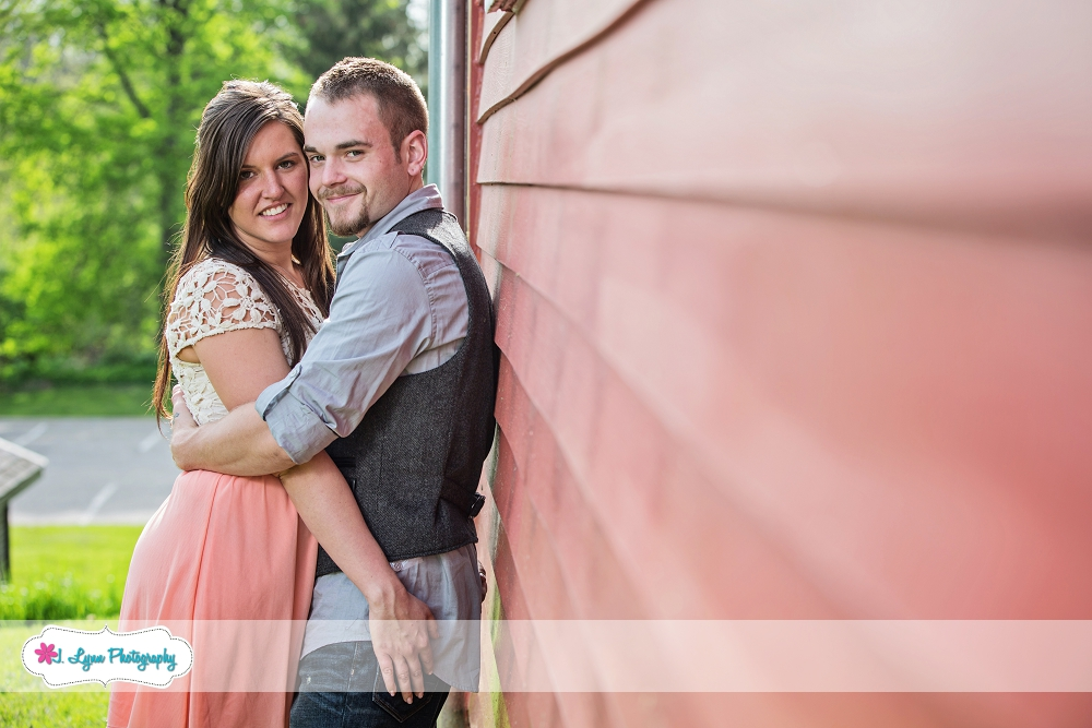 couple leaning against red wall